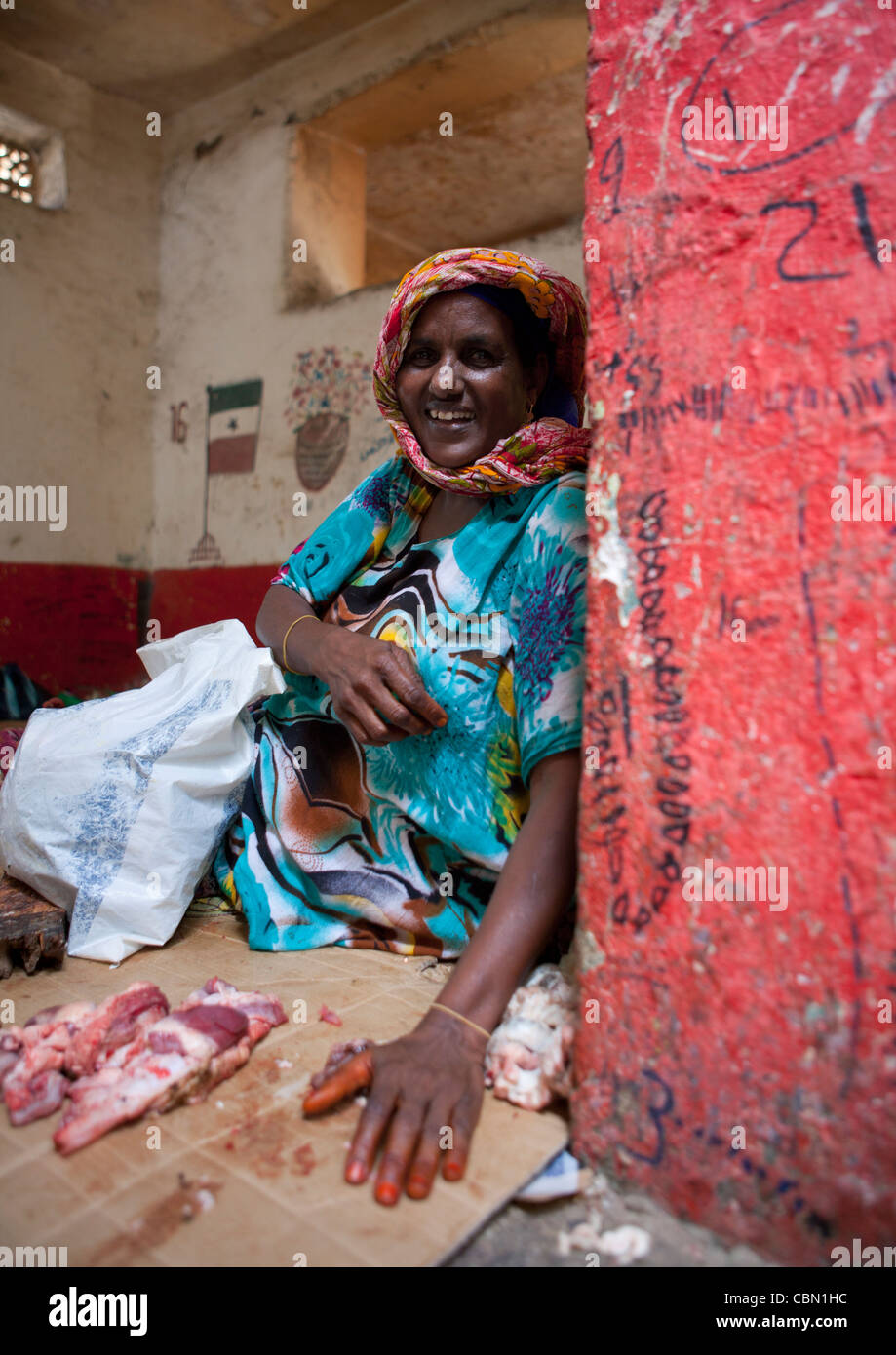 Mature Woman Sat On Floor At Hargeisa Market Meat Seller Butcher Somaliland - Stock Image