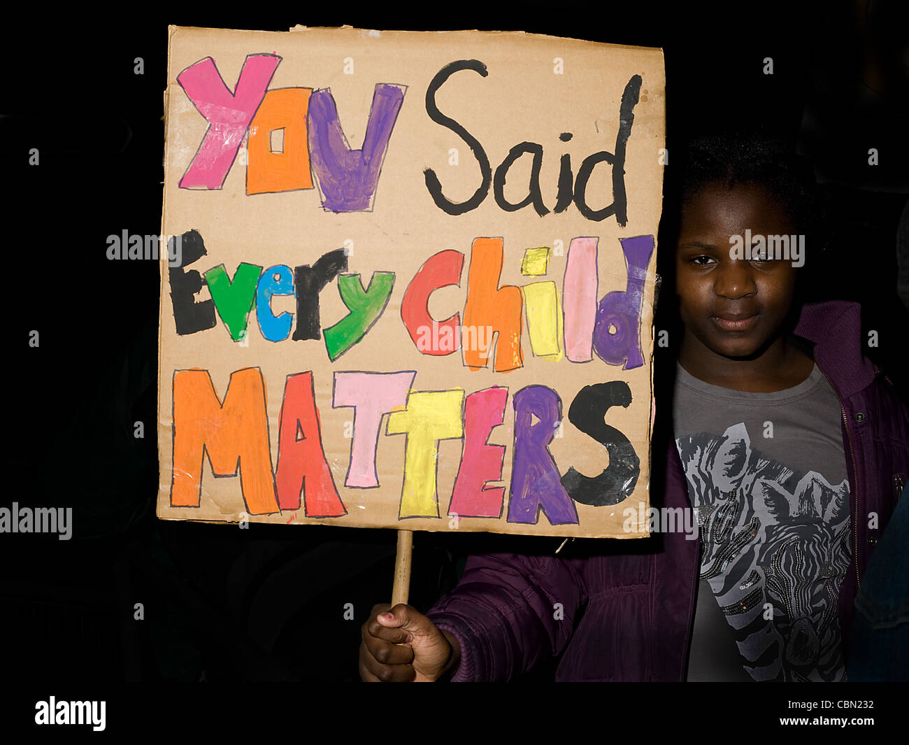 Young black girl hold placard with colorful lettering that reads 'You said Every Child Matters' - Stock Image