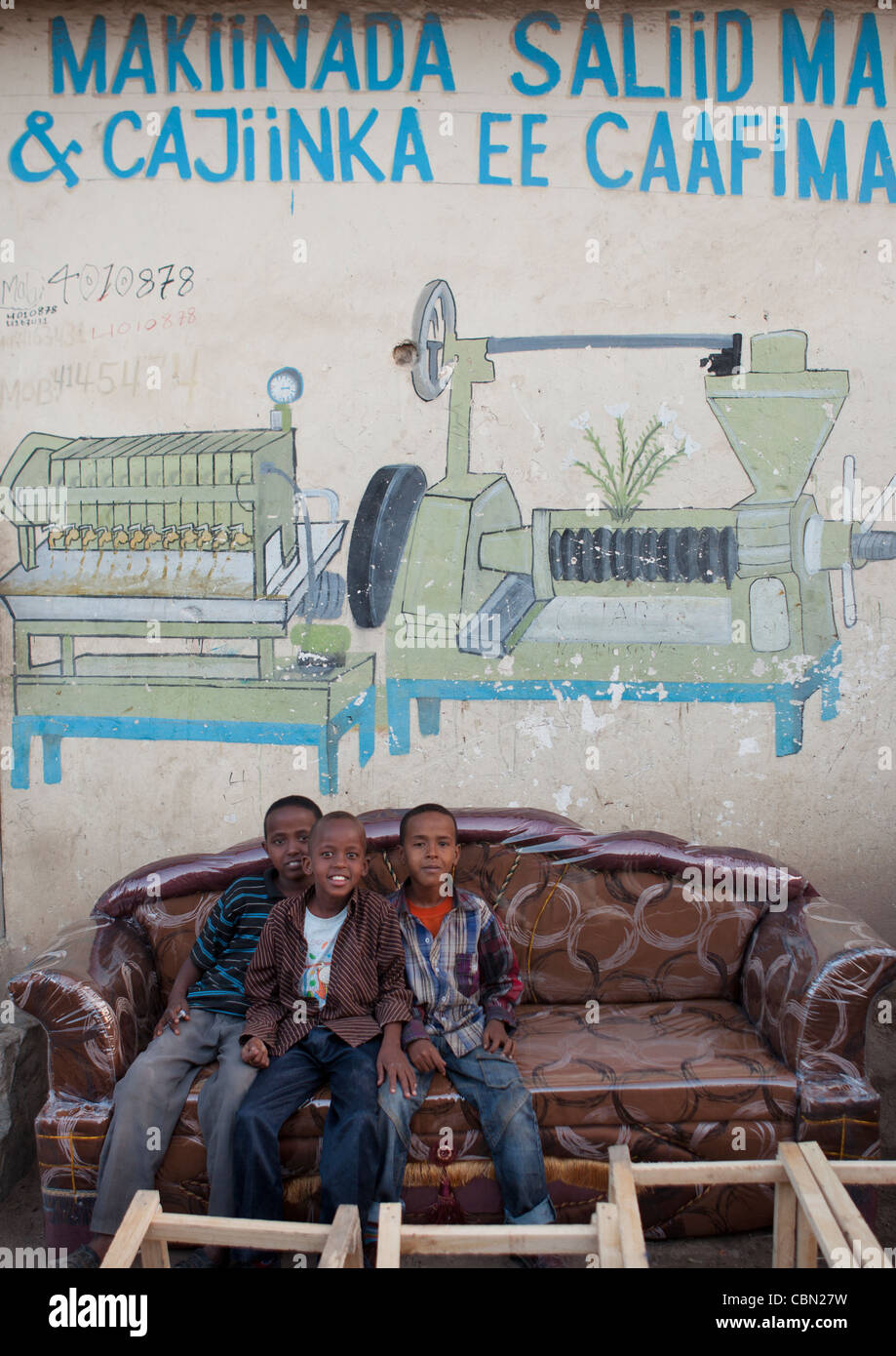Three Children Sitting In Sofa Underneath Advertisement For Factory, Hargeisa Somaliland - Stock Image