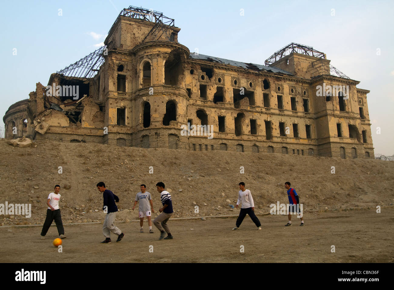 Afghans playing soccer in front of Darul Aman Palace ruined in 1992 Civil War Kabul Afghanistan - Stock Image