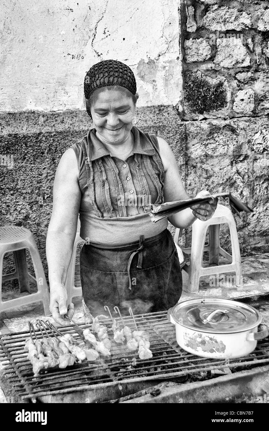 Cooking with local woman on grill for sale in Copan Ruinas Honduras downtown city action Stock Photo
