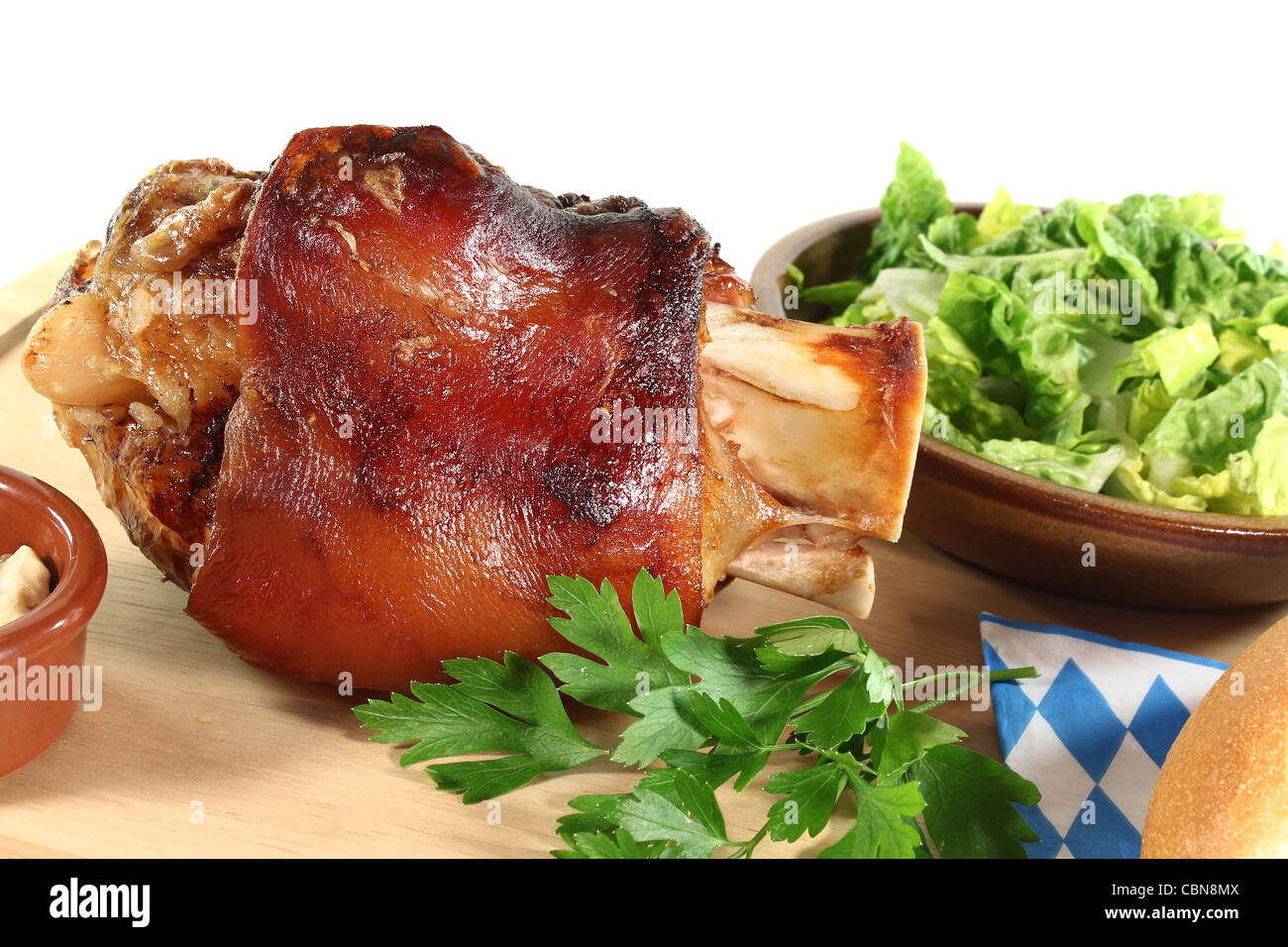 Pork hock with mustard, lettuce and parsley on a board - Stock Image