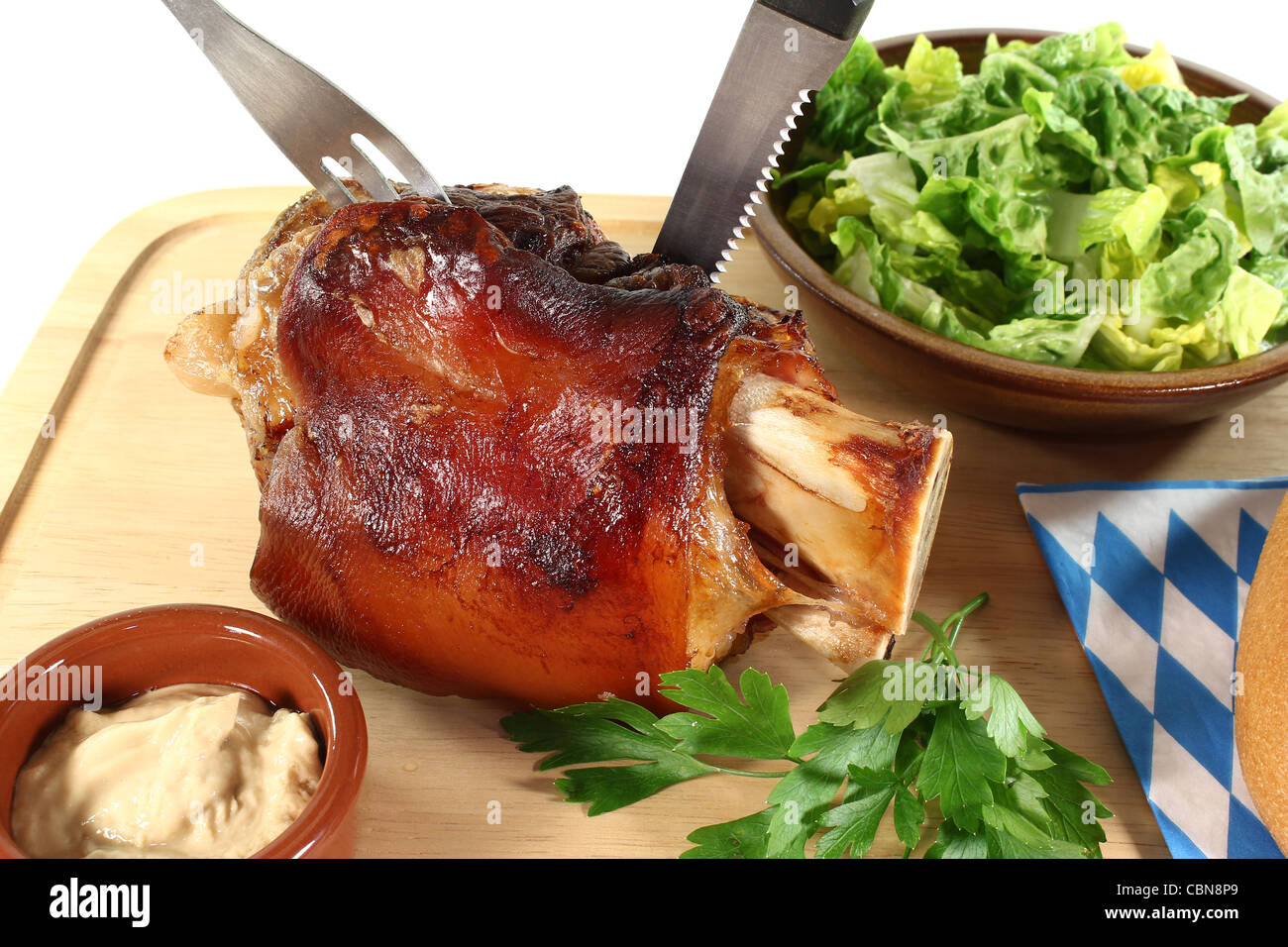 Pork hock with mustard, lettuce and parsley on a board with cutlery - Stock Image