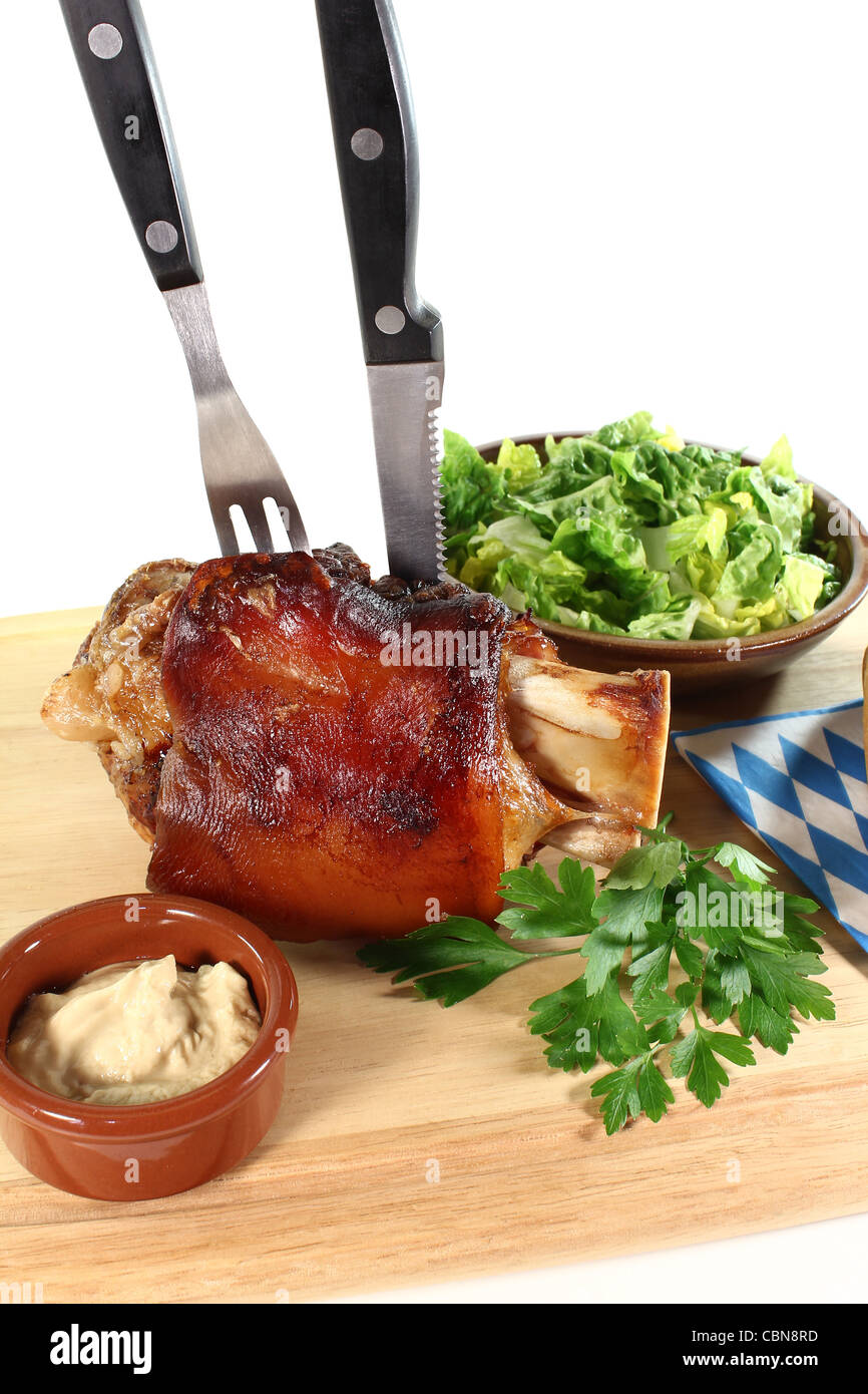 fresh Pork hock with mustard, lettuce and parsley on a board with cutlery - Stock Image