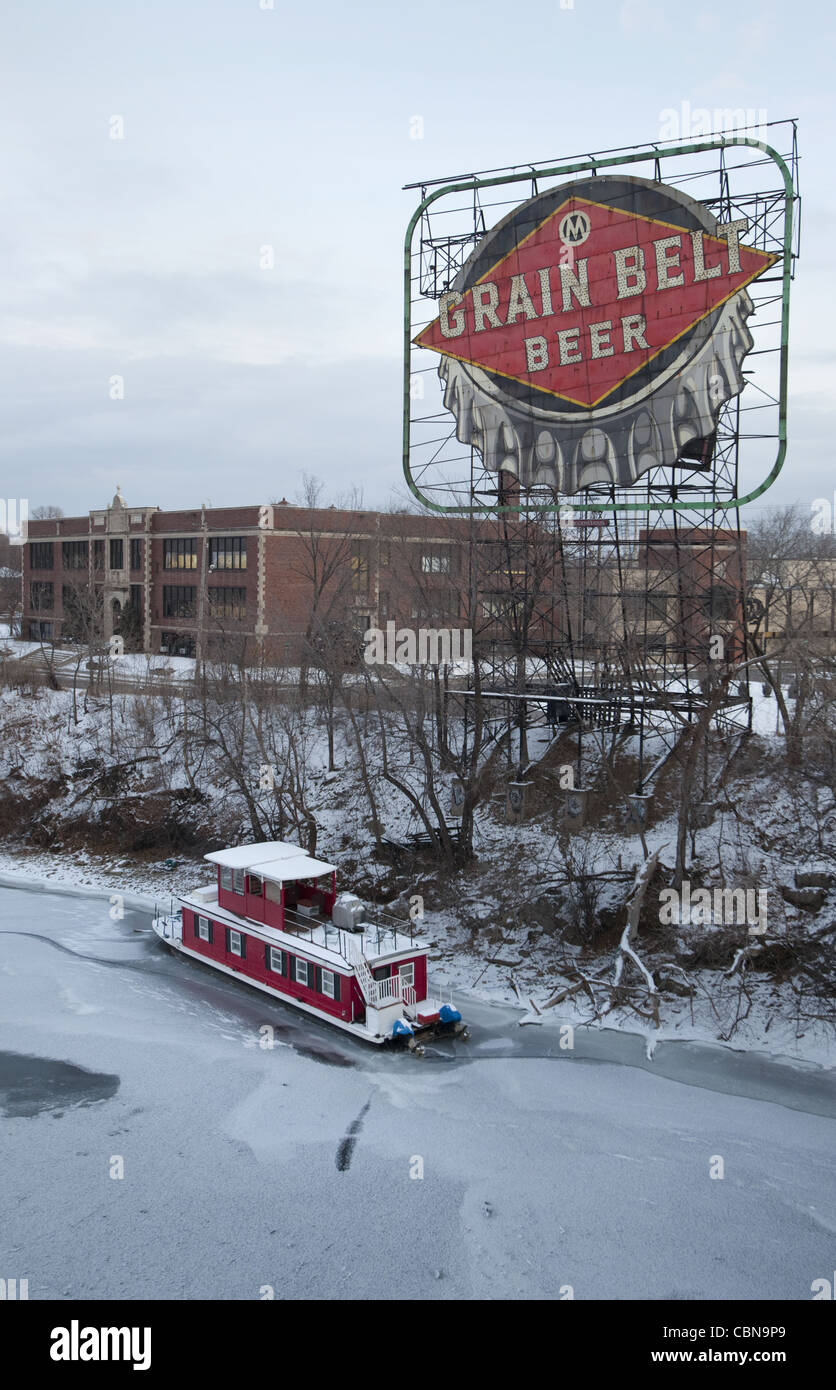 Red houseboat and Grain Belt Beer sign along the Mississippi River in Minneapolis, Minnesota - Stock Image