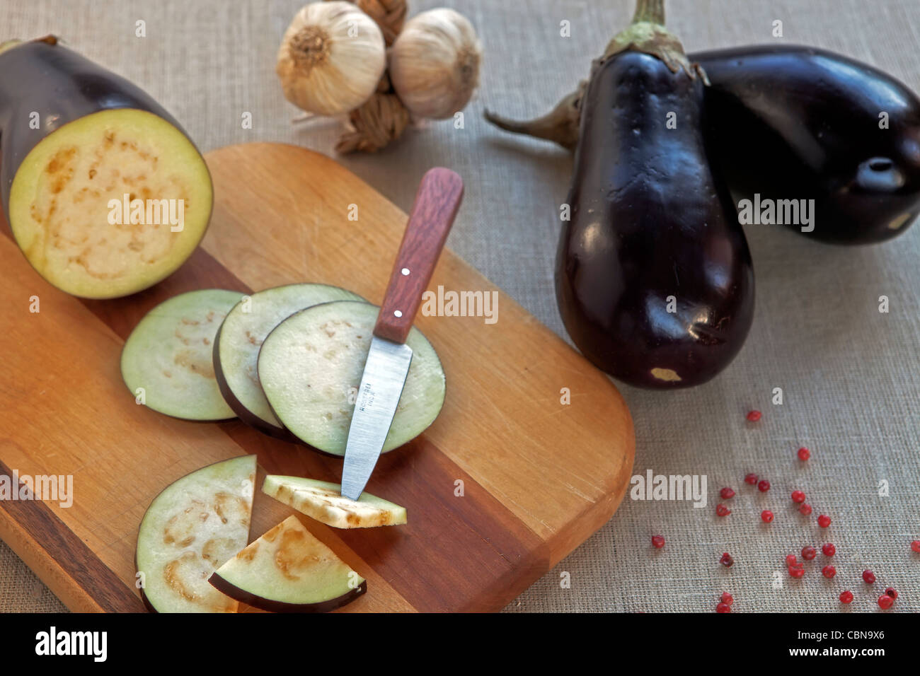 Eggplant, whole and cut, with knife on a wooden board  - Stock Image