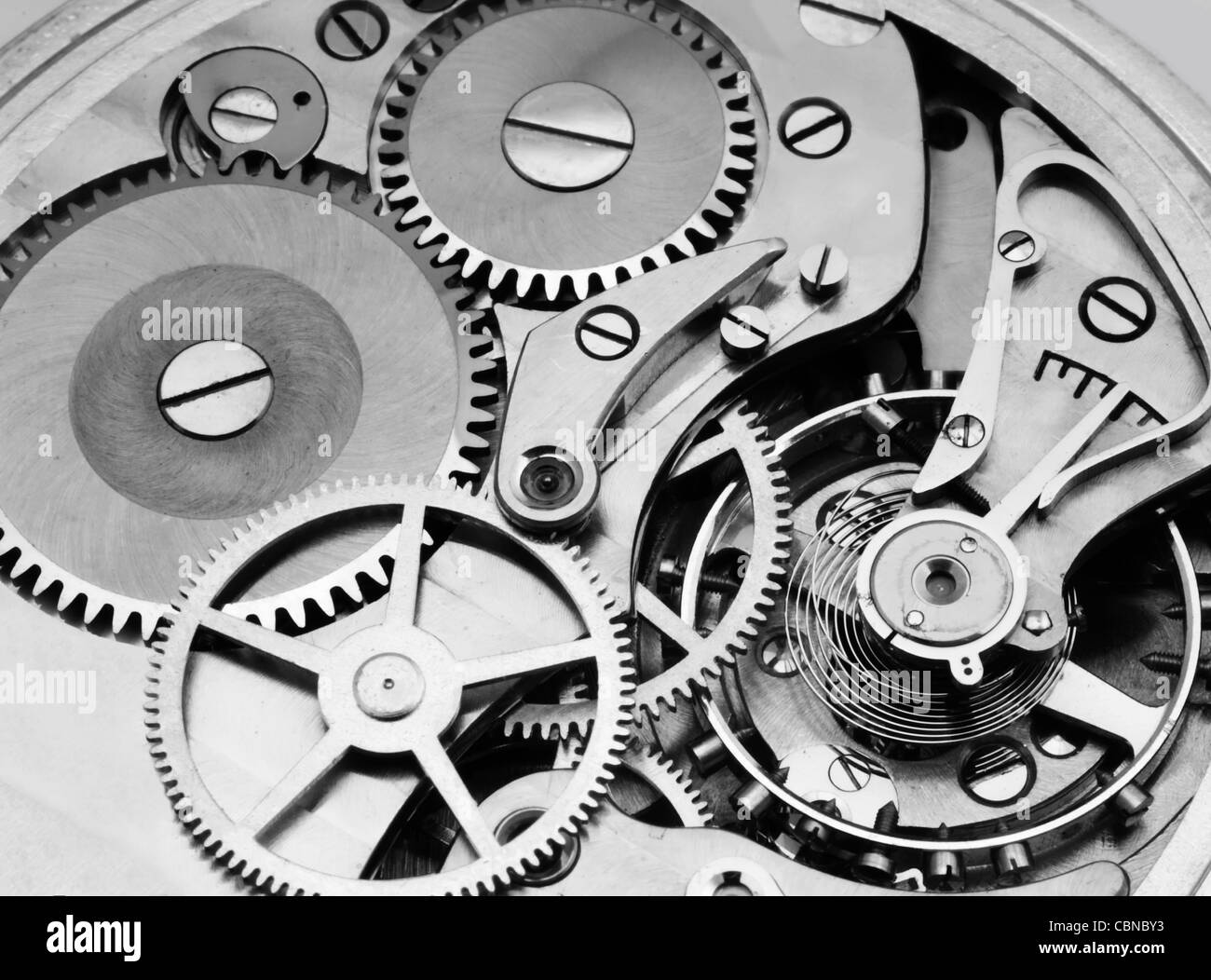 mechanism of a pocket watch timepiece showing  gears and balance wheel - Stock Image