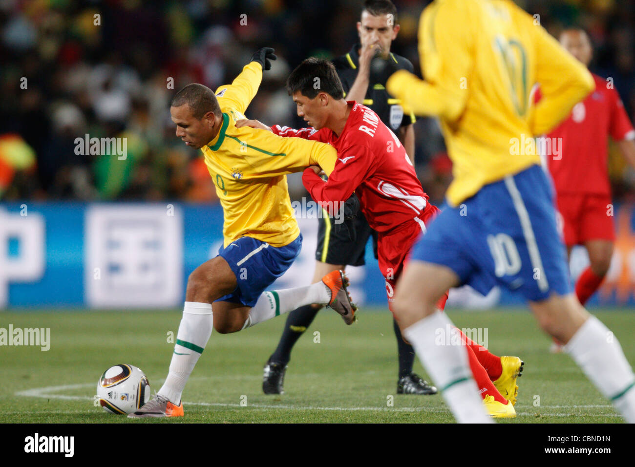 Luis Fabiano of Brazil (L) battles against Kwang Chon Ri of North Korea (R) during a FIFA World Cup match at Ellis - Stock Image