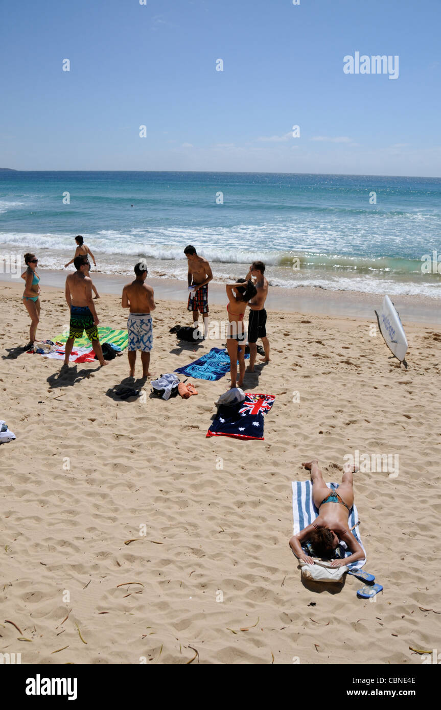 A group of teenagers and a sunbather on Manly Beach facing   the Pacific Ocean near Sydney in Australia. Stock Photo