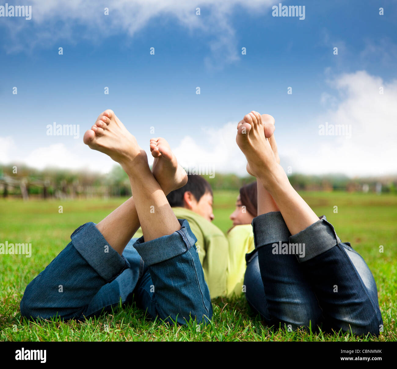 relaxed couple lying on the grass - Stock Image