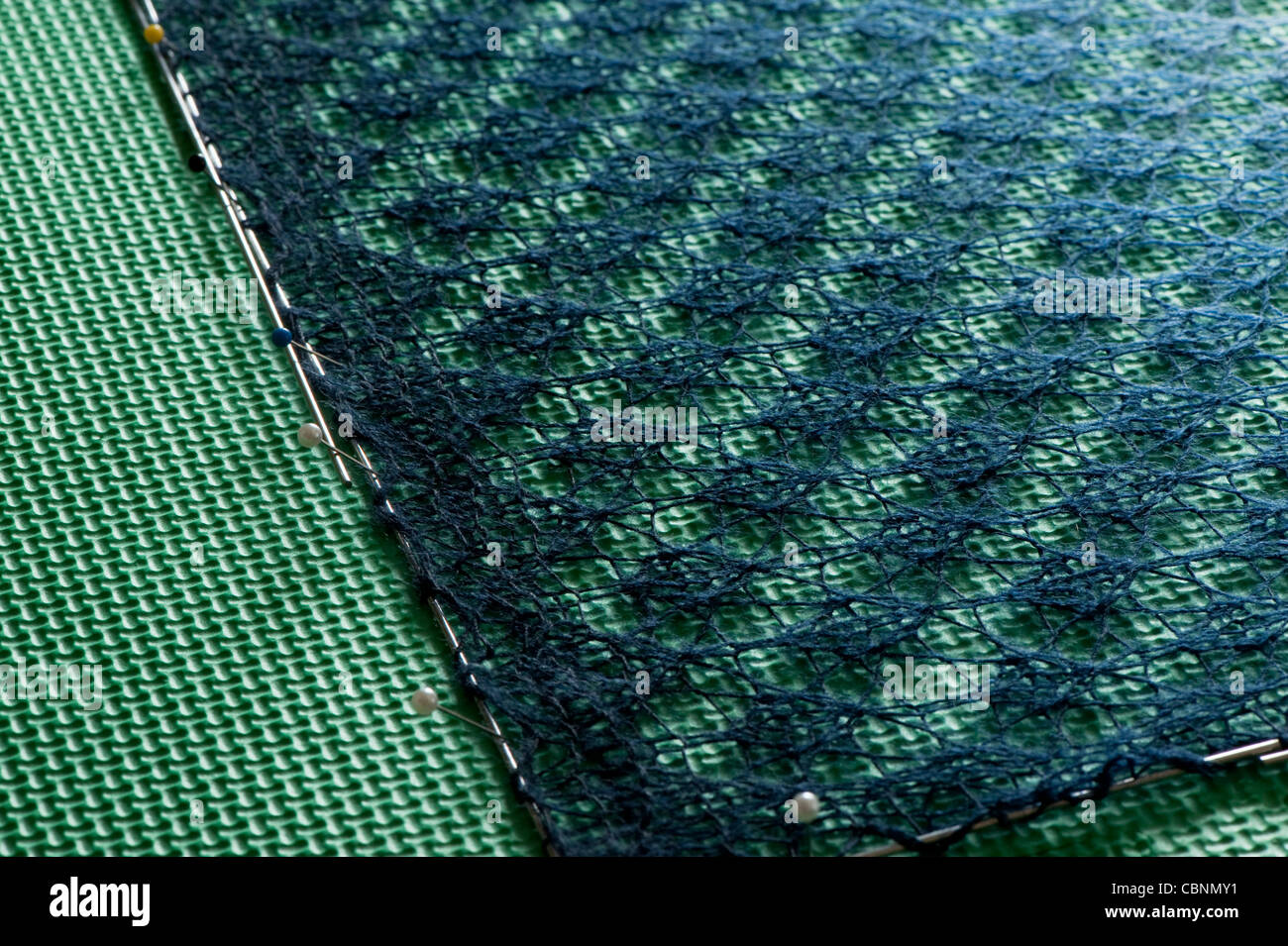 Variegated yarn knitted lace shawl being blocked: dampened and stretched out on foam mats to set and display lace Stock Photo