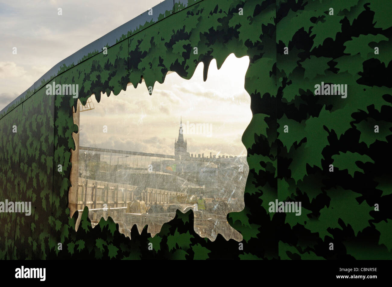 View of St Pancras Station through leaf covered hoardings, the King's Cross Central development site, King's - Stock Image