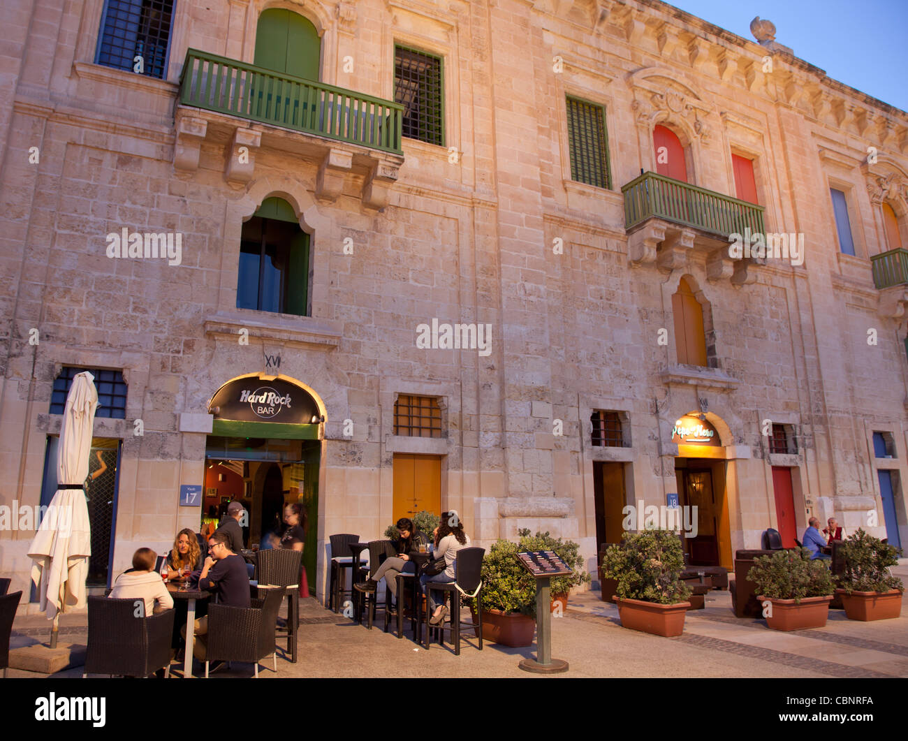 Restored wharf buildings in the Grand Harbour in Valletta that now serve as shops, cafes, clubs, and restaurants. - Stock Image