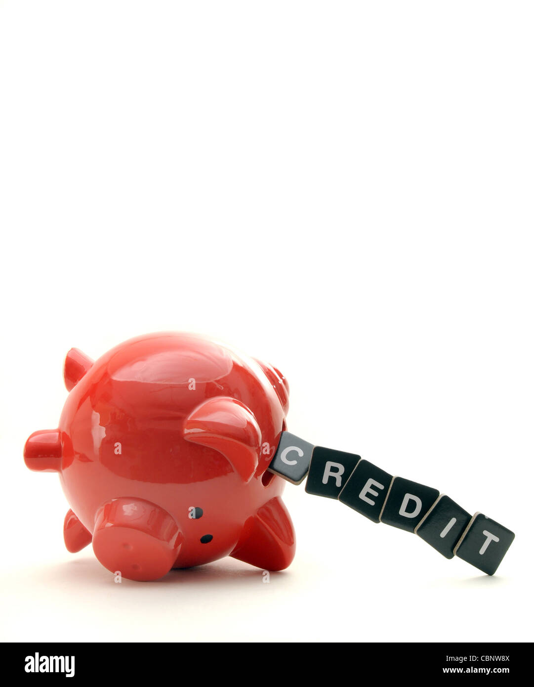 OVERTURNED RED PIGGYBANK WITH LETTERS SPELLING  CREDIT  RE THE ECONOMY CREDIT CRUNCH SAVINGS LOANS DEBT FINANCIAL - Stock Image