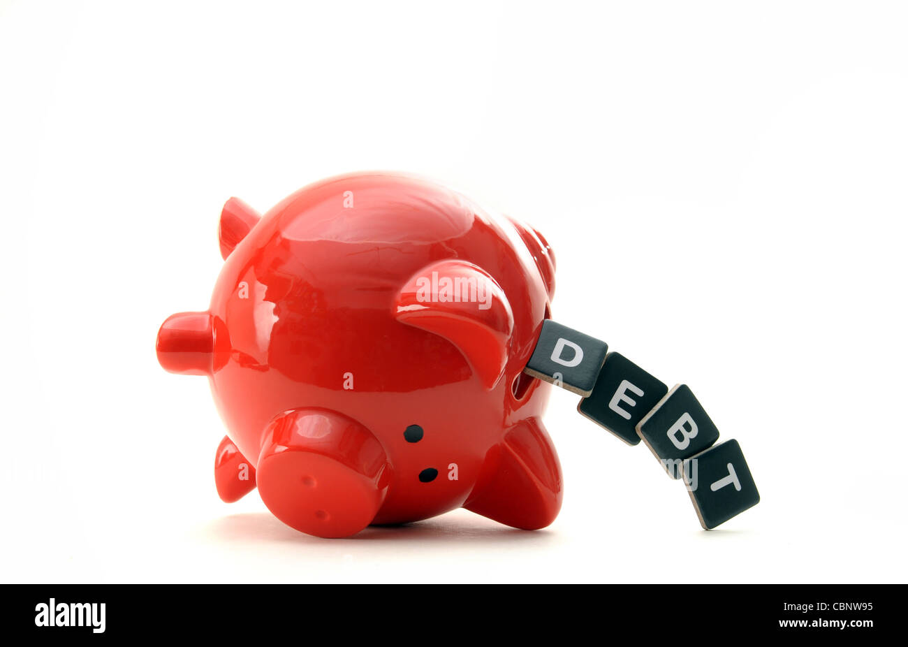 OVERTURNED RED PIGGYBANK WITH LETTERS SPELLING  DEBT  RE THE ECONOMY CREDIT CRUNCH SAVINGS LOANS DEBT FINANCIAL - Stock Image
