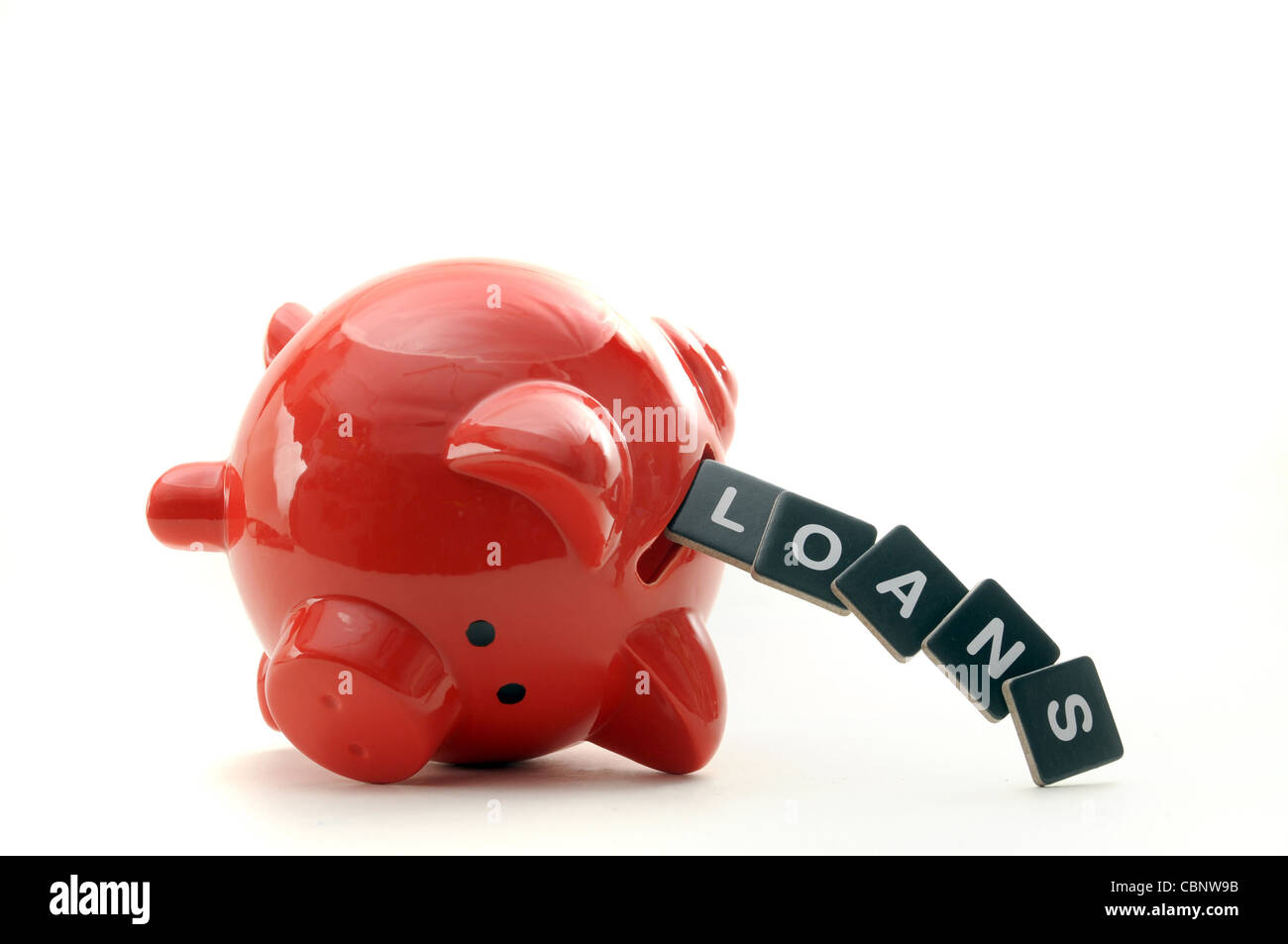 OVERTURNED RED PIGGYBANK WITH LETTERS SPELLING  LOANS RE THE ECONOMY CREDIT CRUNCH SAVINGS LOANS DEBT FINANCIAL - Stock Image