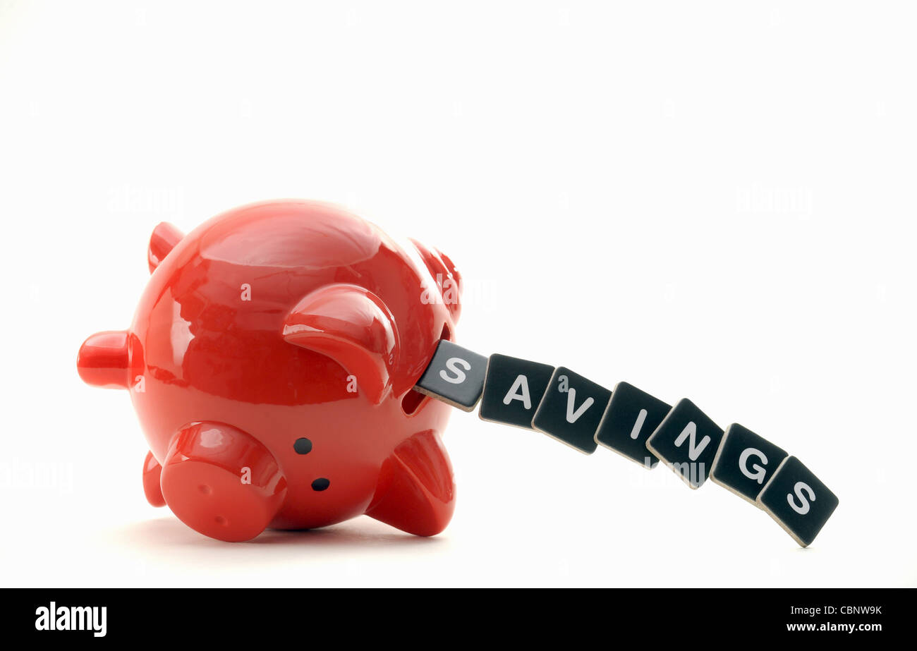 OVERTURNED RED PIGGYBANK WITH LETTERS SPELLING SAVINGS RE                 THE ECONOMY CREDIT CRUNCH SAVINGS LOANS - Stock Image