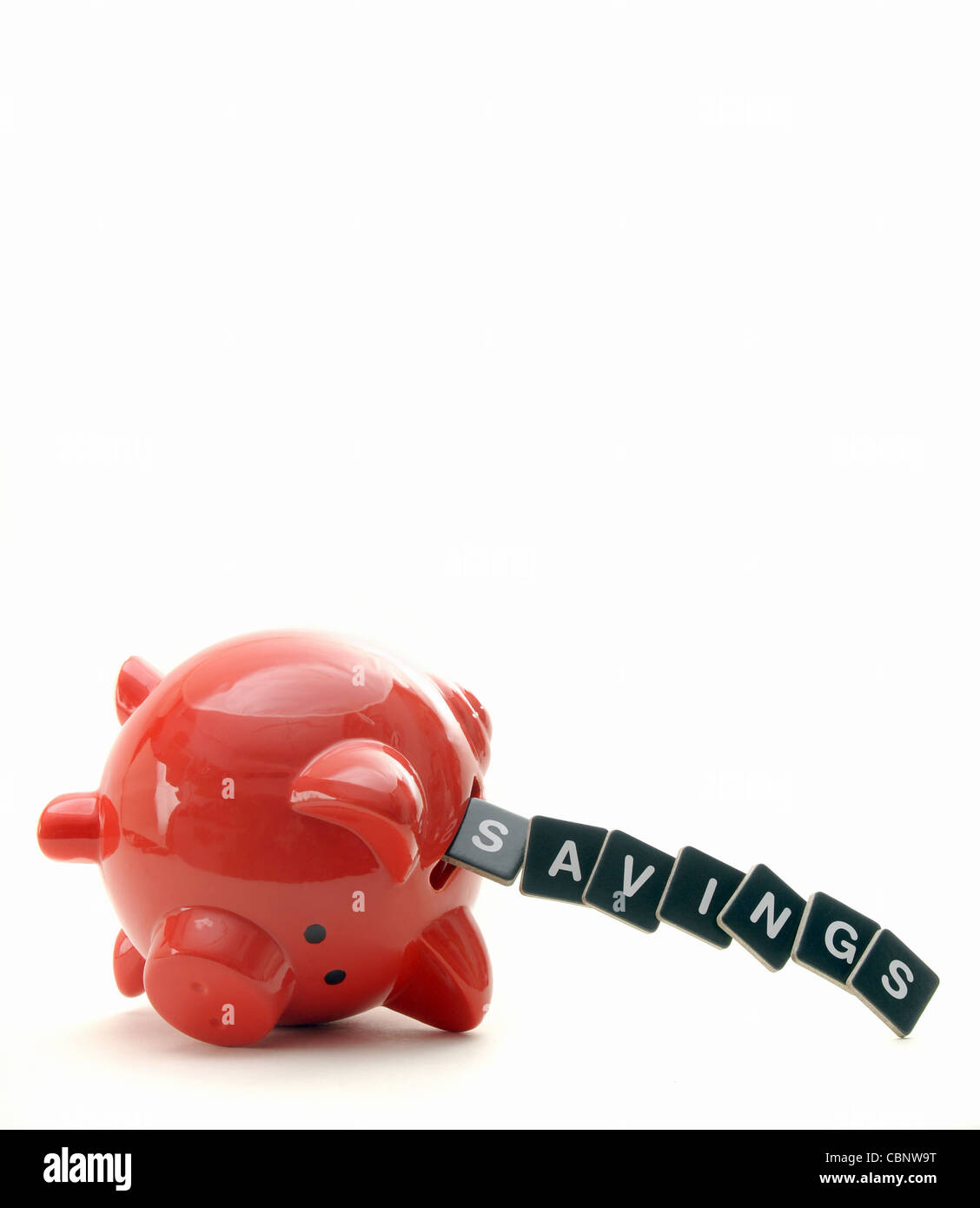 OVERTURNED RED PIGGYBANK WITH LETTERS SPELLING SAVINGS   RE CASH      THE ECONOMY CREDIT CRUNCH SAVINGS LOANS DEBT - Stock Image