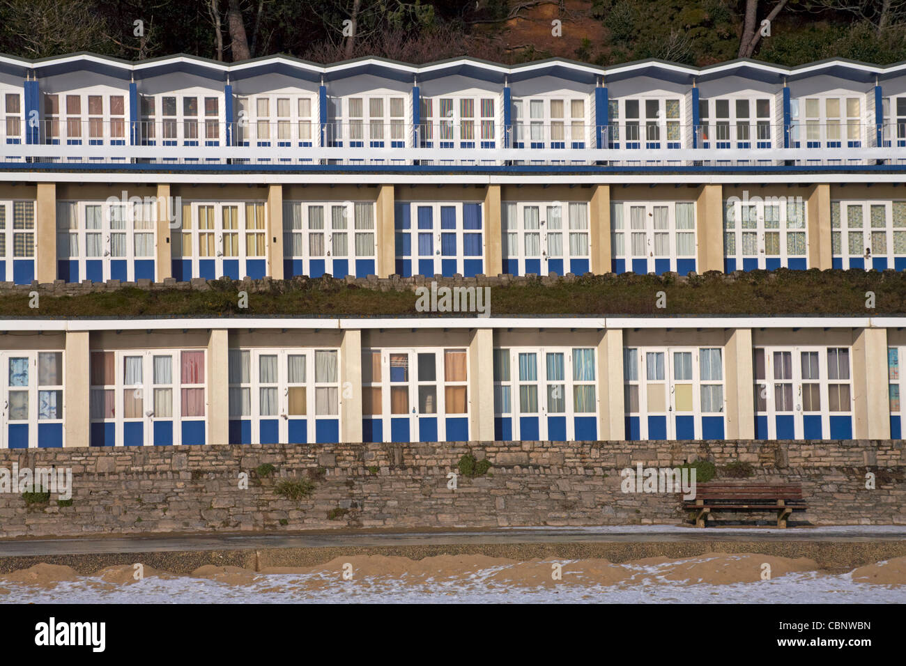 Beach huts at Branksome Dene Chine, Poole with snow on the beach in December Stock Photo
