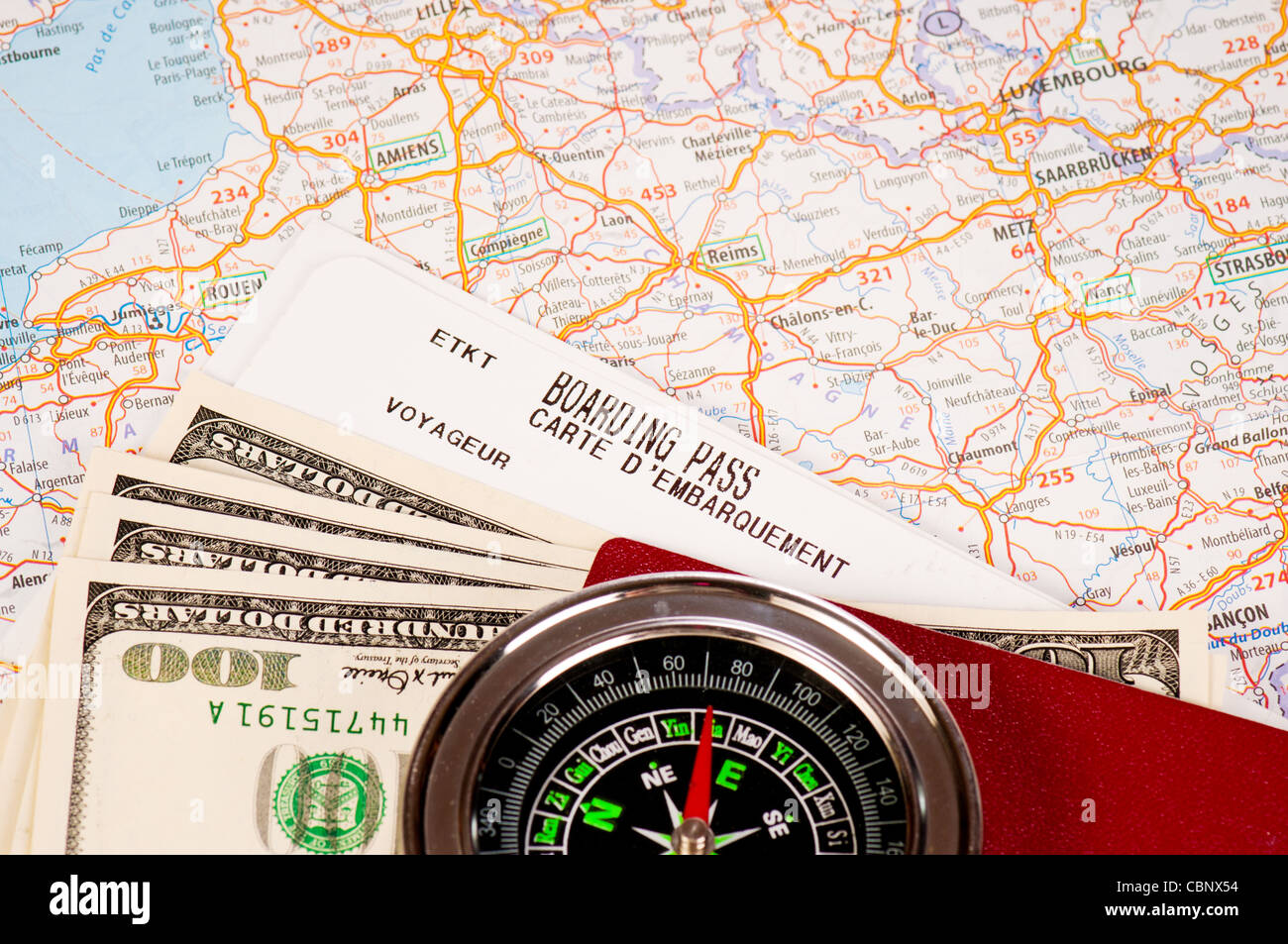 compass, money and passport with boarding pass - Stock Image