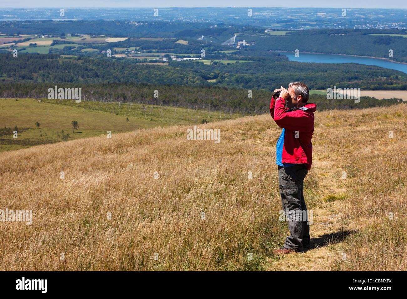 Man with binoculars birdwatching in early summer - Stock Image