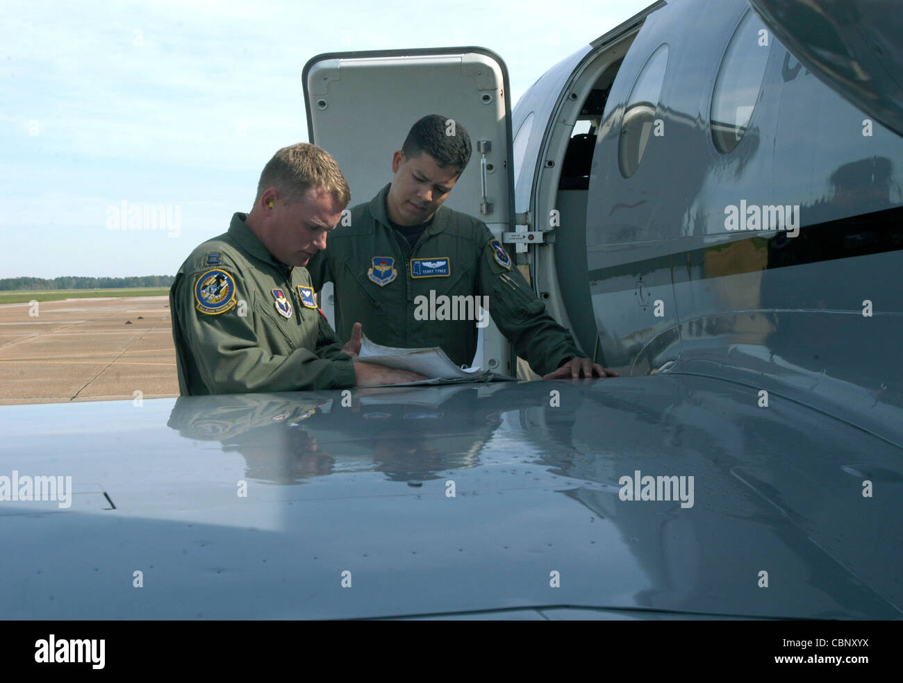 COLUMBUS AIR FORCE BASE, Miss. -- Capt. Stephen Miller (left) reviews aircraft maintenance records with Capt. Terry - Stock Image