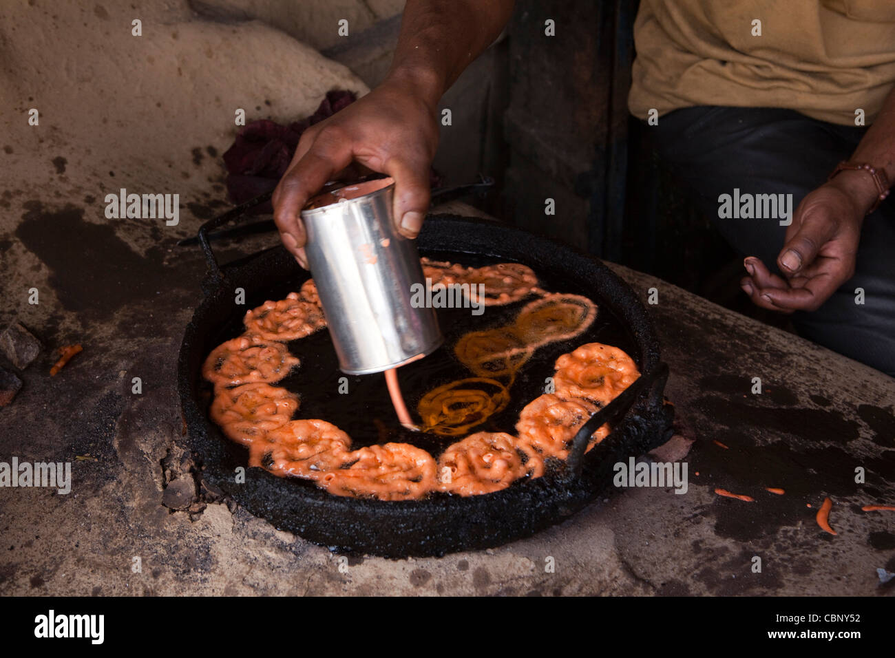 India, Manipur, Lairouching Hills, food, hands of man cooking jelabi in small roadside cafe - Stock Image