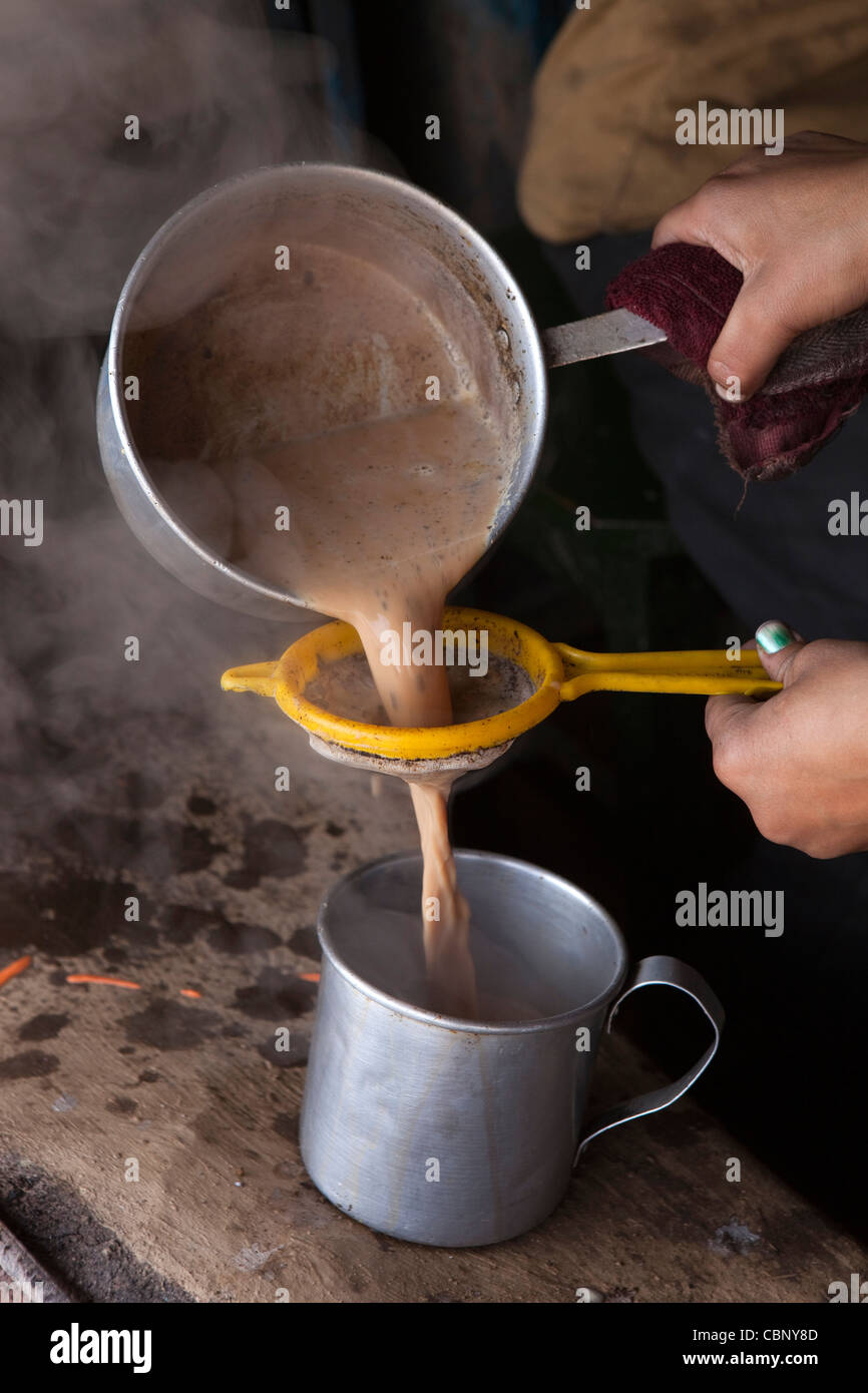 India, Manipur, Lairouching Hills, food, small roadside café, chai (tea) being strained into cup - Stock Image