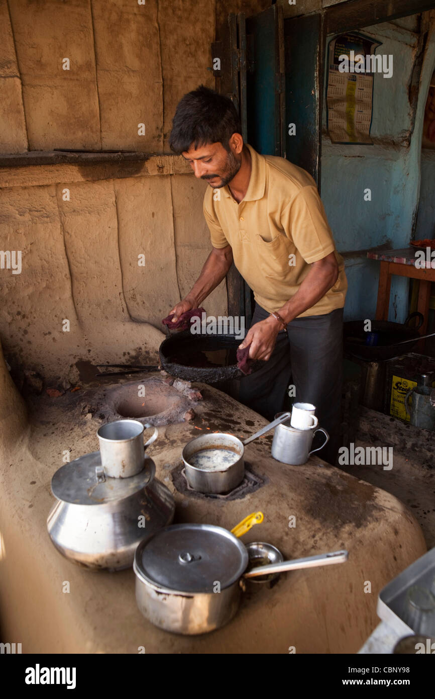 India, Manipur, Lairouching Hills, food, small roadside café, chai (tea) being cooked in saucepan on primitive - Stock Image
