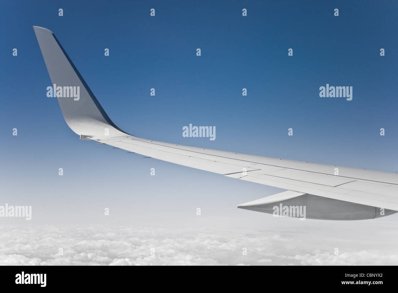 view of the jet plane wing and sky from passenger window - Stock Image