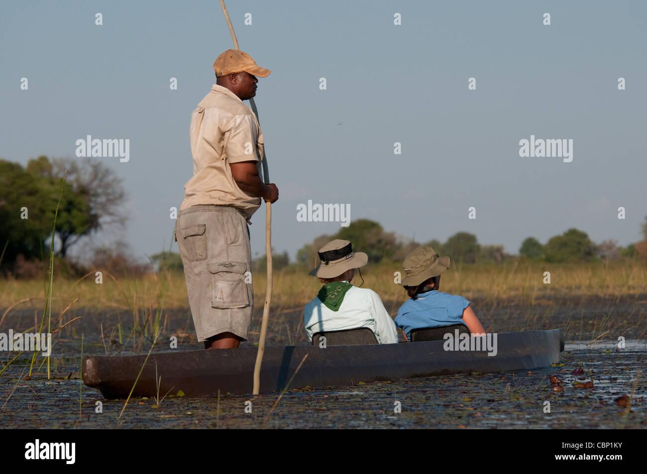 Africa Botswana Okavango Delta-People in Mokoro (dug-out canoe) - Stock Image