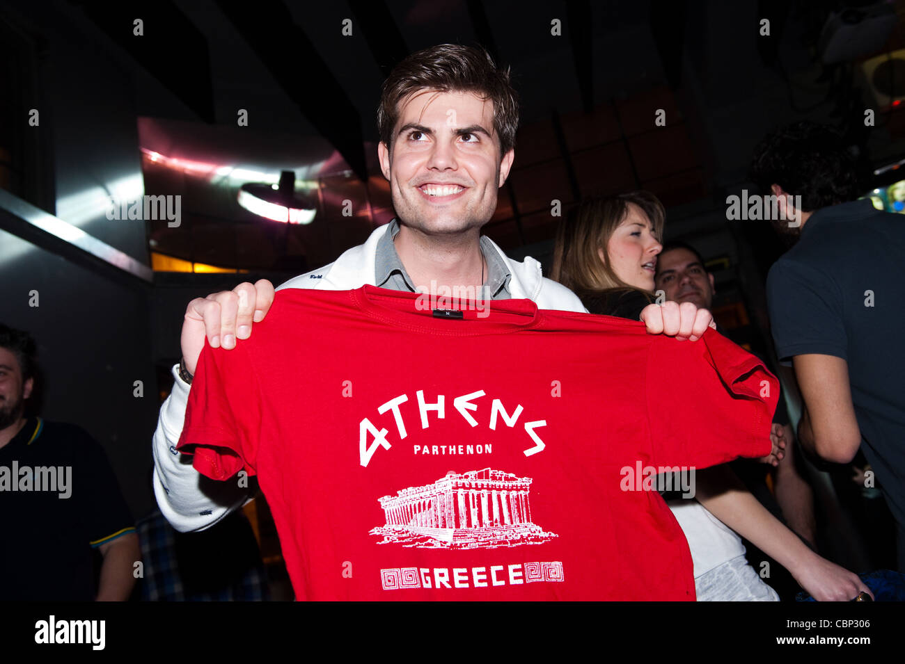 Athenian holding a kitsch t -shirt with the Parthenon on a night out in Bios bar in Gazi area of Athens. - Stock Image