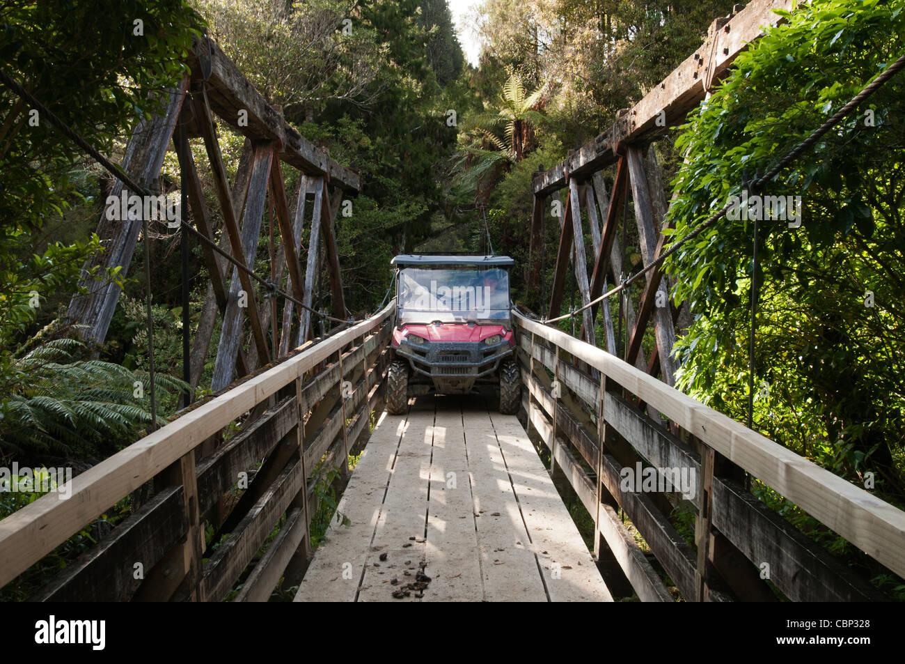 Man driving across wooden bridge in Vehicle - Stock Image