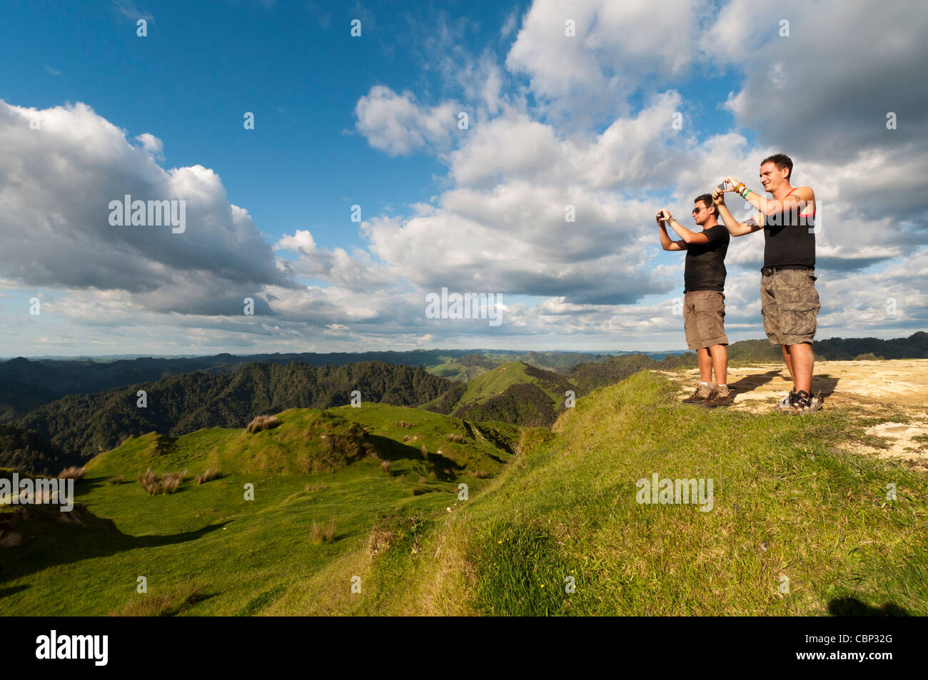 Two young backpackers taking picture with cameras, Blue duck lodge, Whakahoro, Ruapehu District, New Zealand - Stock Image