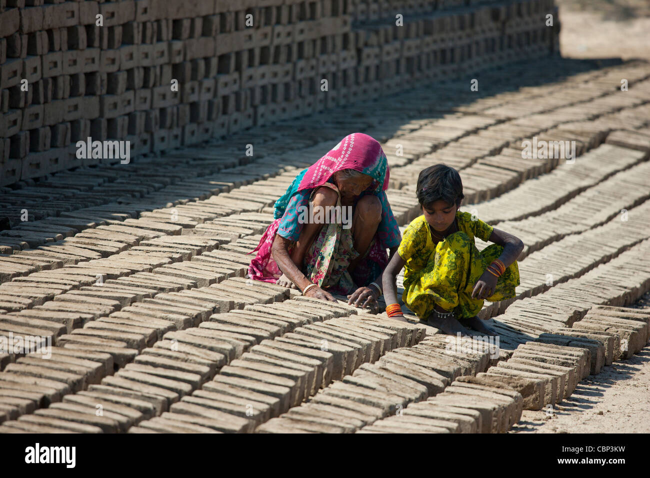 Indian woman with grandchild drying bricks made from clay at Khore Bricks Factory, Rajasthan, Northern India - Stock Image