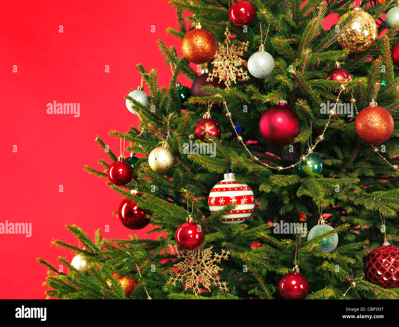 Closeup of Christmas tree colorful decoration on bright red background - Stock Image