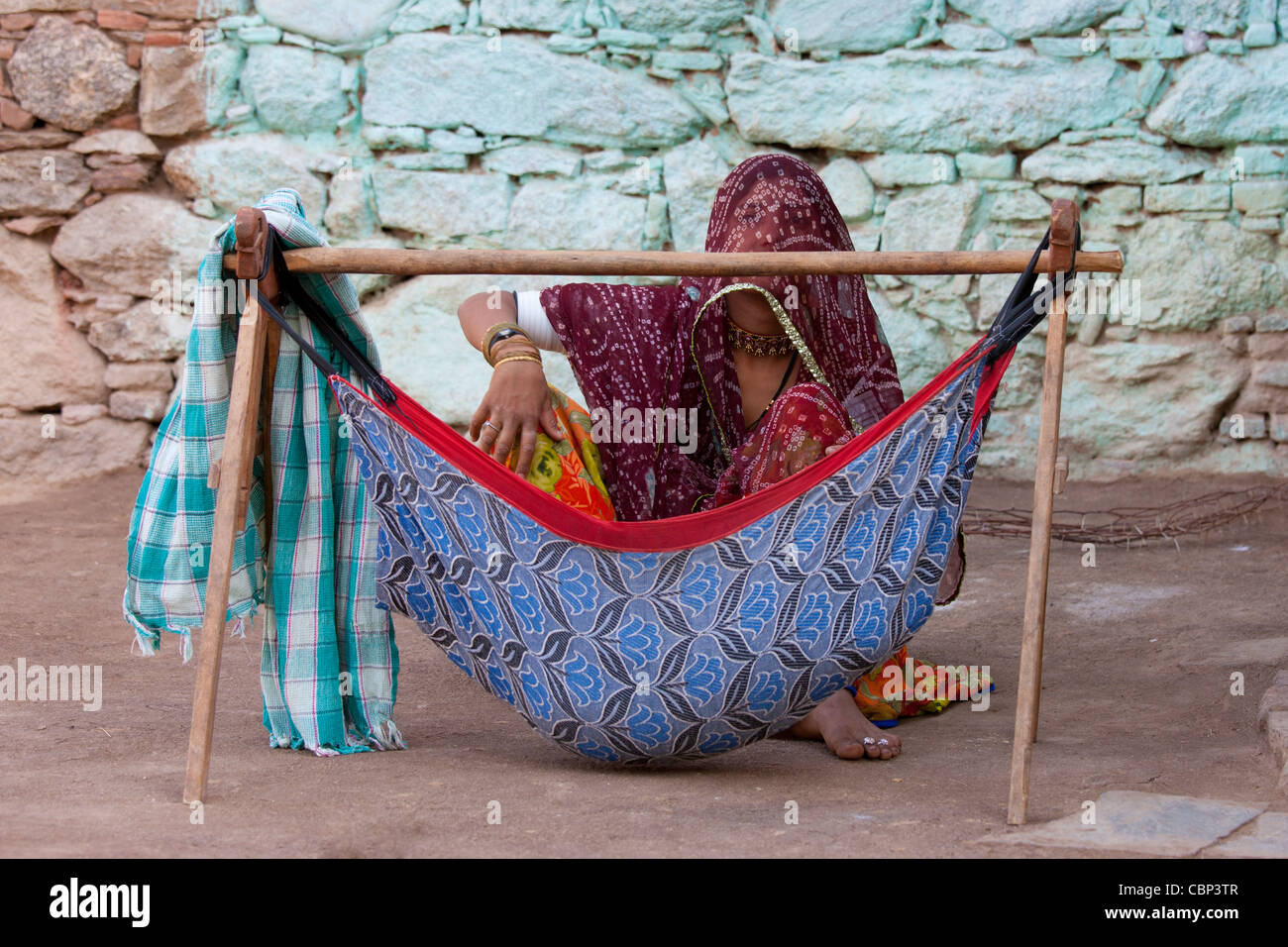 Young Indian woman with her child in hammock at home in Narlai village in Rajasthan, Northern India - Stock Image