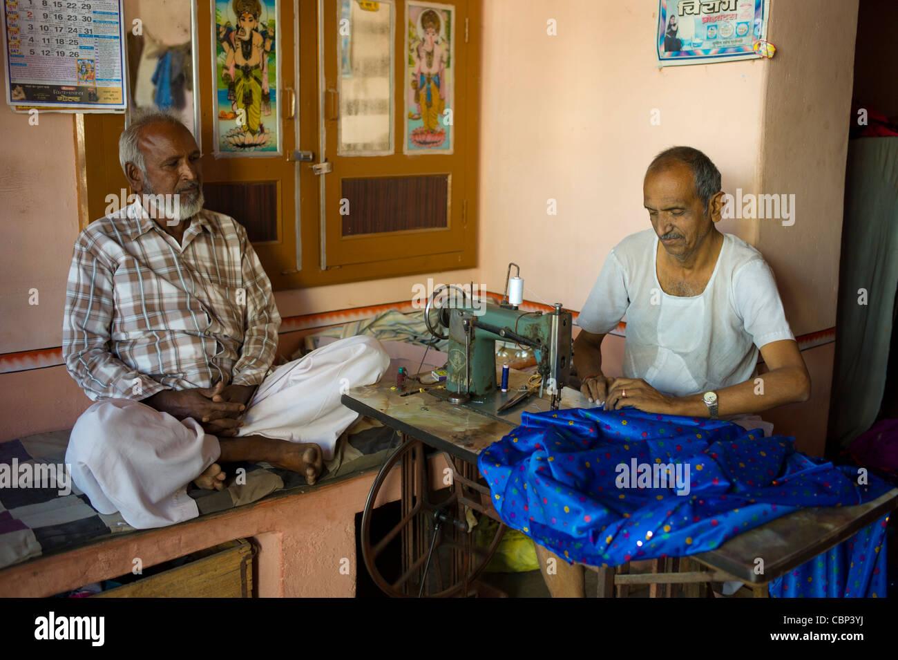 Indian man with old sewing machine making sari in Narlai village in Rajasthan, Northern India Stock Photo