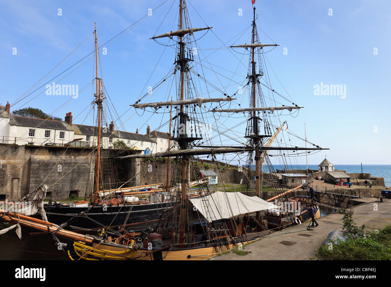 Pheonix and other Tall Ships in the inner harbour with old cottages on the quayside. Charlestown, Cornwall, England, - Stock Image