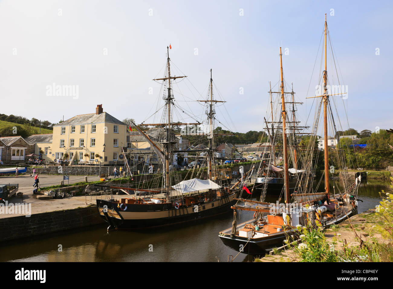 Charlestown, Cornwall, England, UK, Britain. Tall ships in the inner harbour with the Pier House Hotel on the quayside - Stock Image