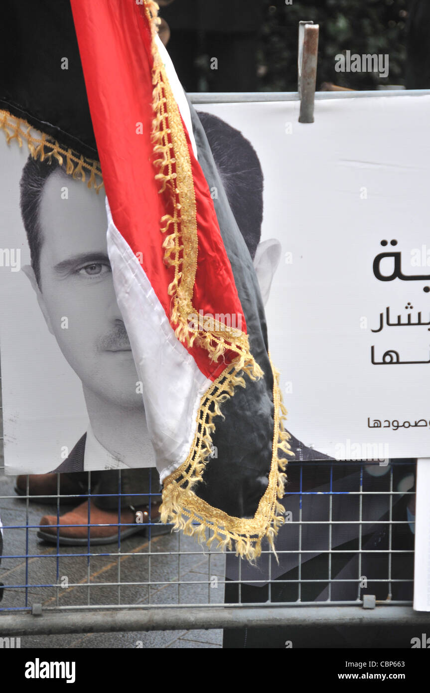 Bashar al-Assad President of Syria poster and flag at an anti Assad protest outside the American Embassy London - Stock Image
