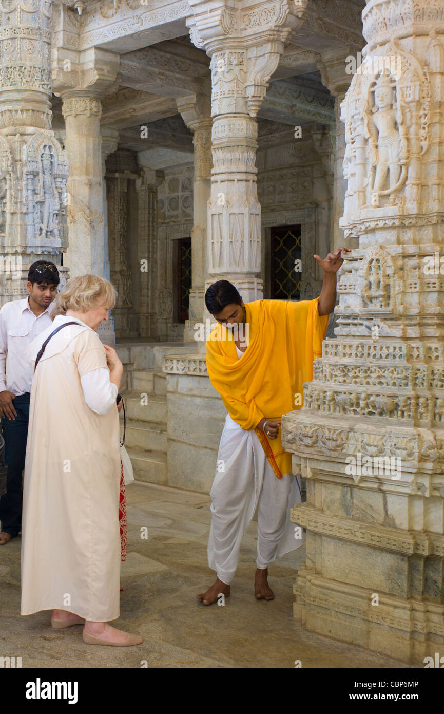 Temple priest shows tourists stone carving detail at The Ranakpur Jain Temple at Desuri Tehsil of Rajasthan, India - Stock Image