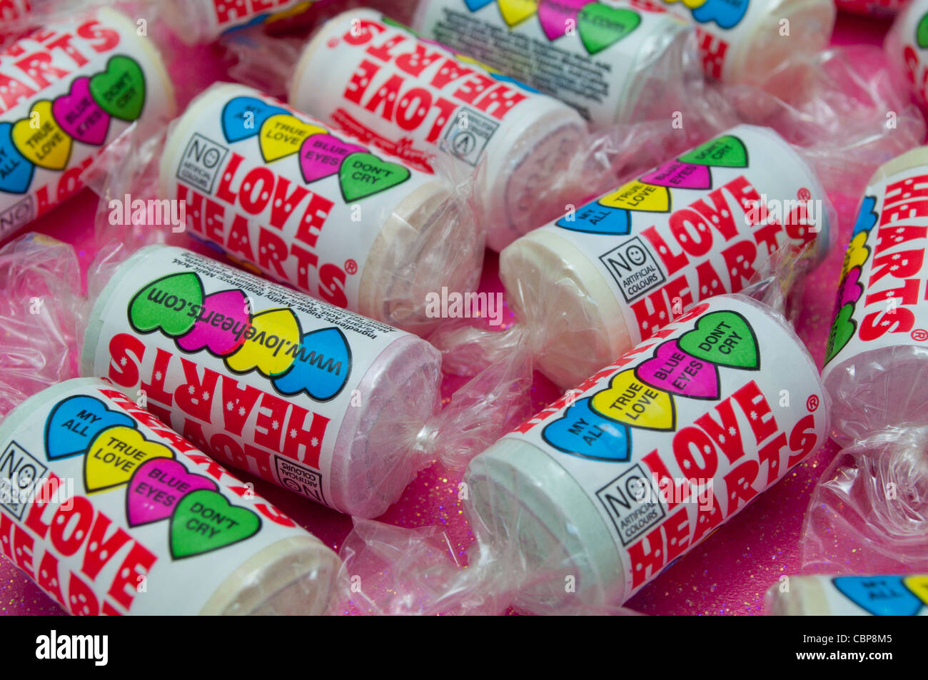 Close up of tubes of Love Heart candy sweets on a sparkly pink background with selective focusing - Stock Image