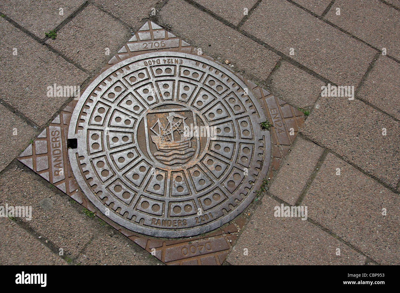 Denmark, Helsingoer. Downtown manhole cover with traditional ship crest design. - Stock Image