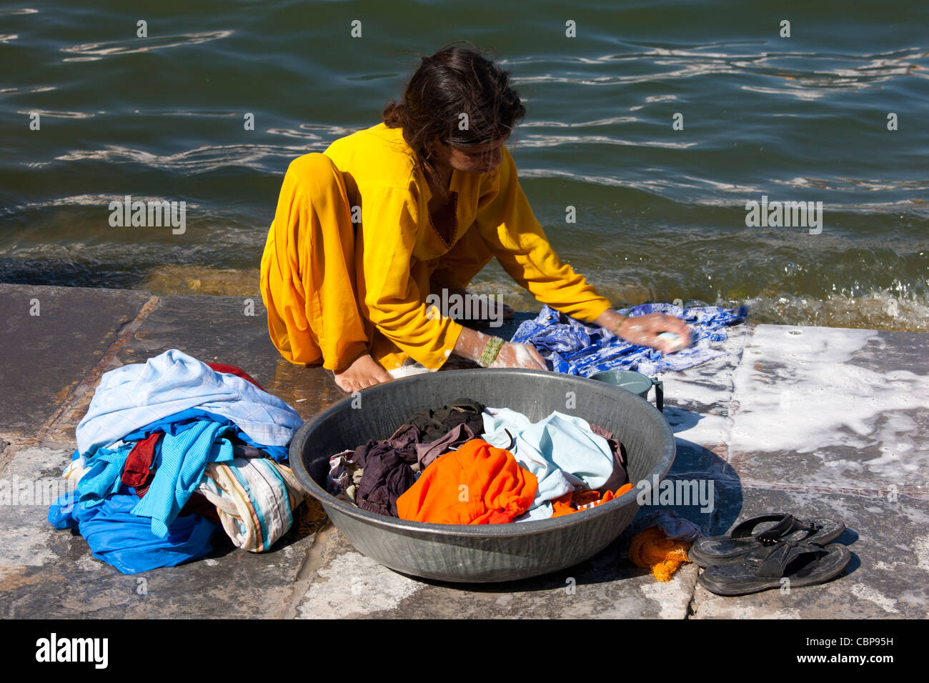 Young Indian girl squatting down to do her laundry in the waters of Lake Pichola, Udaipur, Rajasthan, Western India - Stock Image