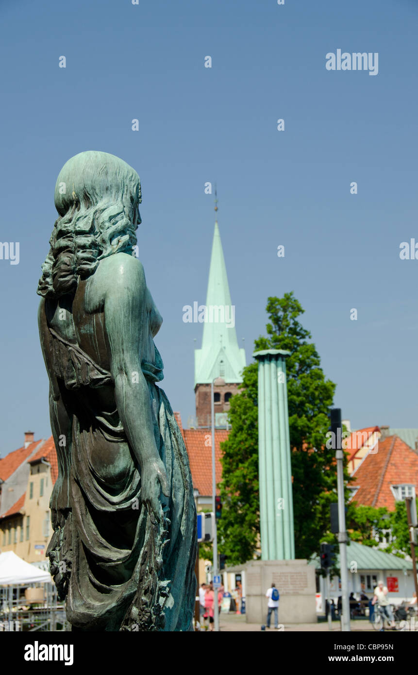 Denmark, Helsingoer. Downtown statue with church steeple in distance. - Stock Image