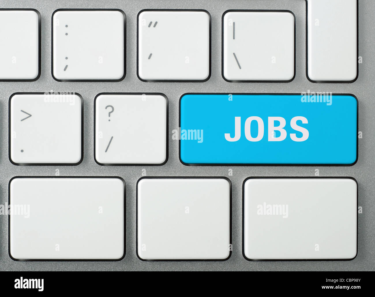 Job search. Laptop keyboard and blue key 'JOBS' on it. Studio shot. - Stock Image