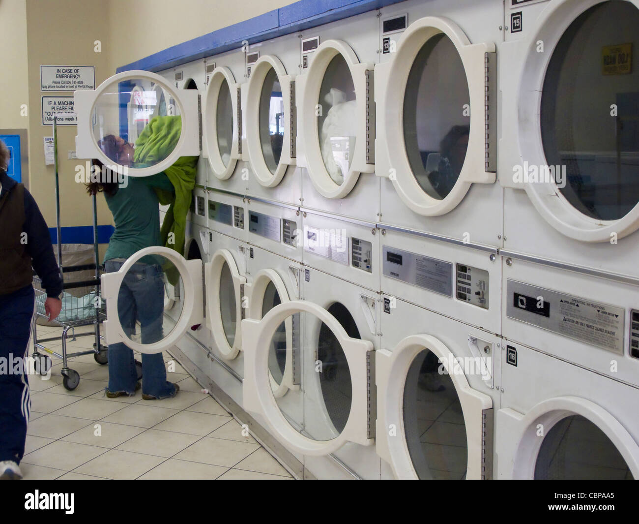 Woman loading dryer in laundromat - Stock Image