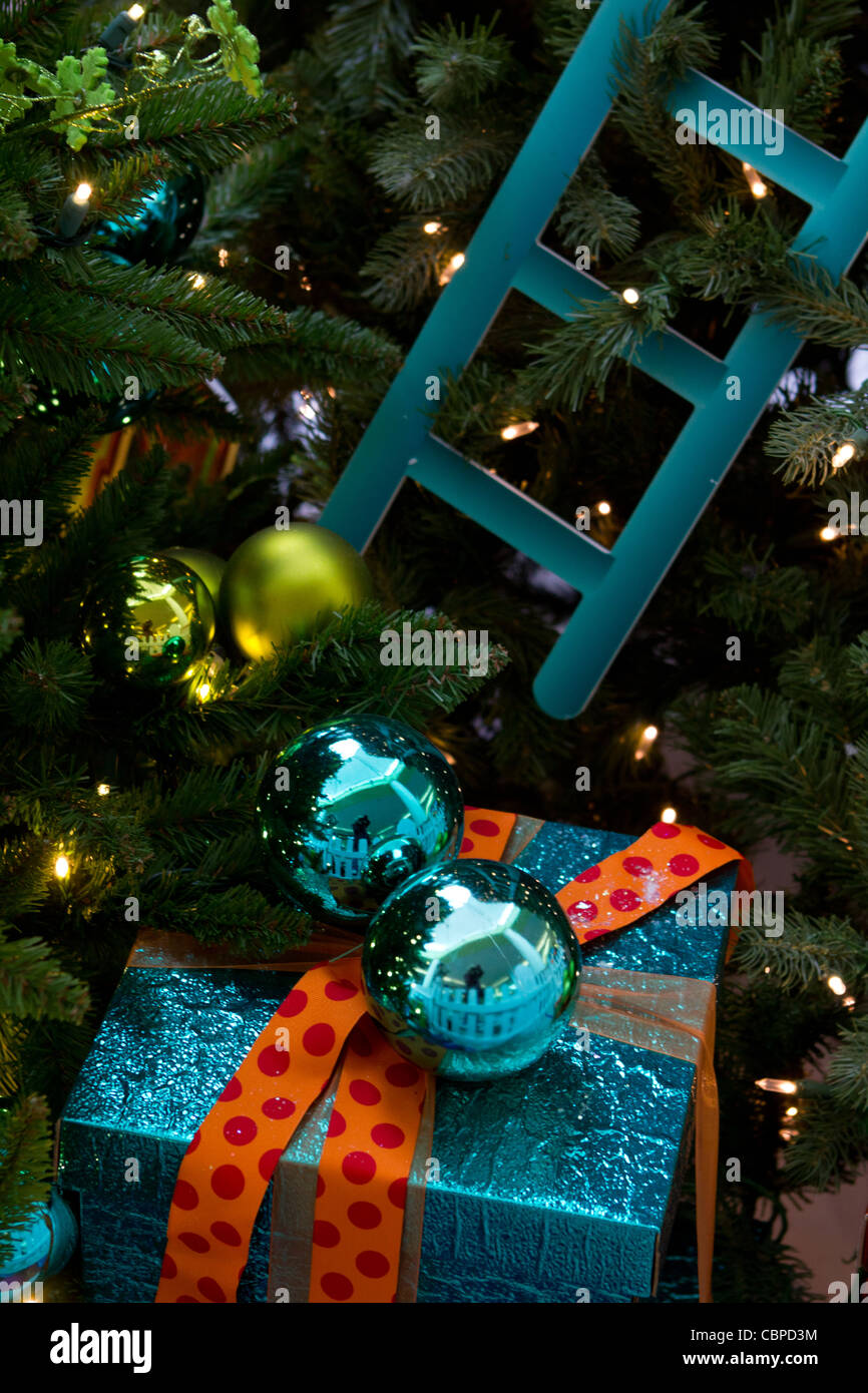 christmas present in the pretty wrapping with orange ribbons and 2 blue glass balls under the christmas tree