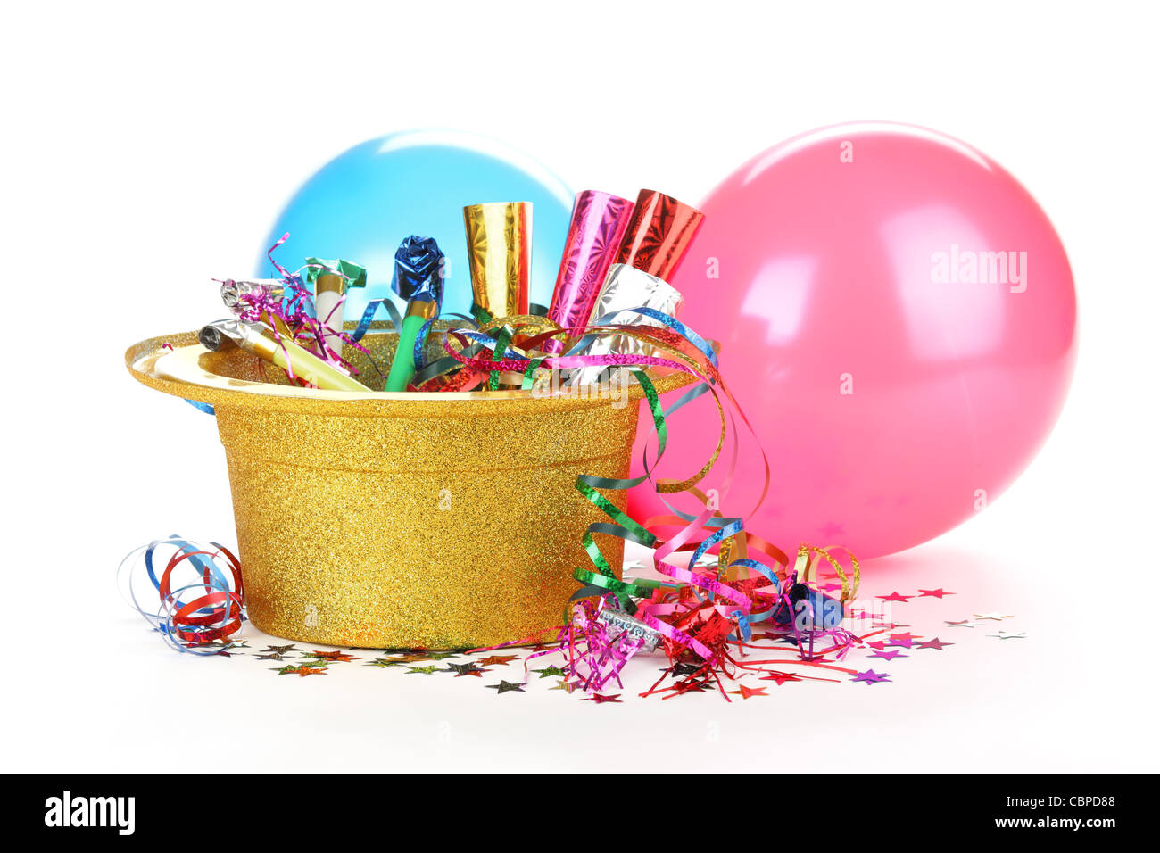 New Year's hat filled with noise makers, streamers and balloons on white background. - Stock Image